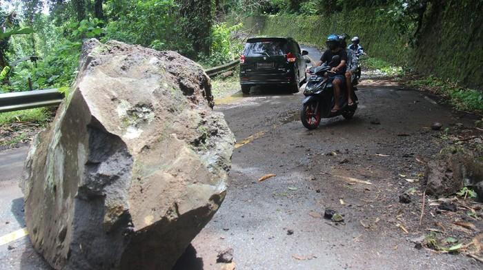 Sejumlah pengendara menghindari batu besar yang longsor dan menutup sebagian jalan lingkar di Pulau Ternate, Kota Ternate, Provinsi Maluku Utara, Sabtu (17/7/2021). Longsor batu besar dari gunung tersebut mengganggu arus lalu lintas, dan insiden terjadi akibat curah hujan yang tinggi melanda Kota Ternate sejak Jumat (16/7) . ANTARA FOTO/Harmoko Minggu/FBA/nz.