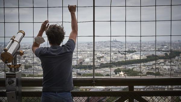 Seorang pengunjung melihat ke arah cakrawala Paris dari setengah Menara Eiffel di Paris, Prancis.