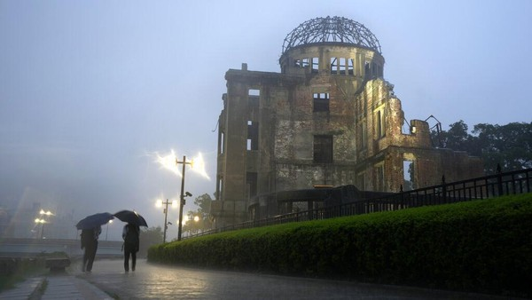 Orang-orang berjalan di dekat Monumen Perdamaian Hiroshima di Hiroshima, Jepang barat.