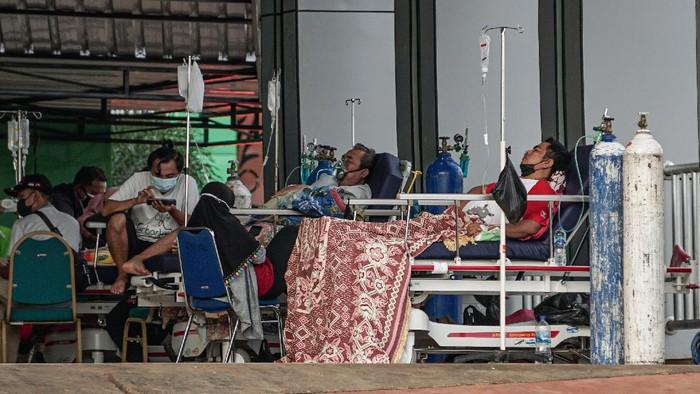 Sejumlah pasien berada di teras gedung Instalasi Gawat Darurat (IGD) Rumah Sakit Umum Daerah (RSUD) Jayapura, Papua, Jumat (16/7/2021). Wakil Direktur Umum dan Keuangan RSUD Jayapura dr Silwanus Sumule mengaku kapasitas ruangan di rumah sakit sudah terisi penuh, hasil antigen pasien yang reaktif diberikan tempat diluar gedung. ANTARA FOTO/Indrayadi TH/hp.