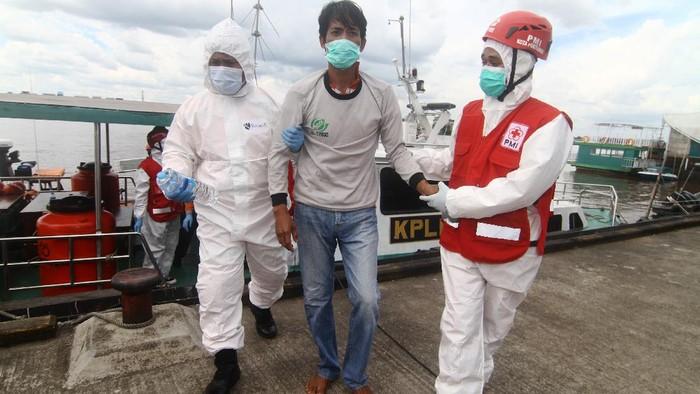 Dua petugas medis menuntun Purwanto (tengah), awak Kapal Motor Usaha Abadi  yang selamat dari kecelakaan kapal tenggelam saat tiba di dermaga Pelabuhan Kantor Kesyahbandaran dan Otoritas Pelabuhan Pontianak, Kalimantan Barat, Jumat (16/7/2021). Hingga saat ini Basarnas masih melakukan pencarian terhadap 44 awak dari 16 kapal motor yang tenggelam di Perairan Kalbar akibat cuaca buruk pada Selasa (13/7/2021) malam dan Rabu pagi (14/7/2021). ANTARA FOTO/Jessica Helena Wuysang/hp.