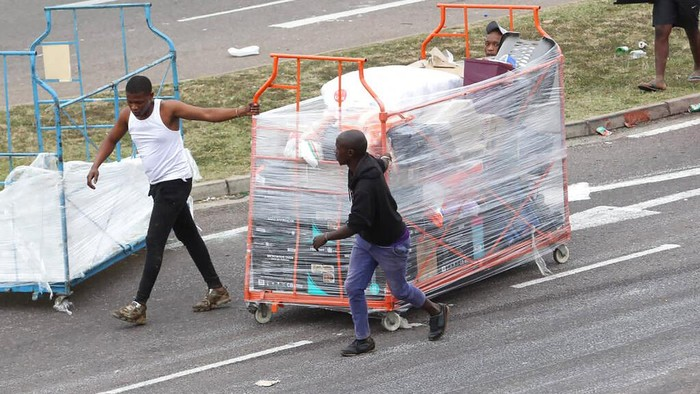 Fast food staff members collect kitchen equipment that was discarded by looters at a trashed shopping mall in Soweto in Johannesburg, South Africa, Tuesday, July 13, 2021. South Africa's rioting continued Tuesday with the death toll rising to 32 as police and the military struggle to quell the violence in Gauteng and KwaZulu-Natal provinces. The violence started in various parts of KwaZulu-Natal last week when Zuma began serving a 15-month sentence for contempt of court. (AP Photo/Themba Hadebe)