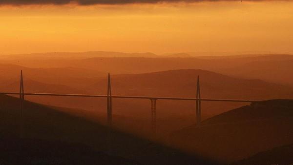 Penampakan matahari terbenam di jembatan Millau Viaduct, Prancis. Jembatan kabel yang mulai dibangun pada akhir tahun 2001 dan dibuka pada tanggal 14 Desember 2004 ini memiliki tinggi tiang mencapai 343 meter. Jembatan ini pun merupakan salah satu jembatan tertinggi di dunia. Pascal Le Segretain/Getty Images.