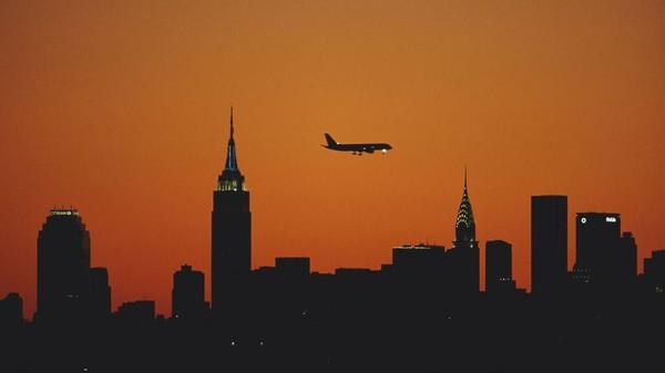 Pemandangan bangunan Empire State Building di Kota New York, Amerika Serikat, dengan latar matahari terbenam kian memesona karena dipotret tepat saat sebuah pesawat tengah mengudara. Jamie Squire/Getty Images.