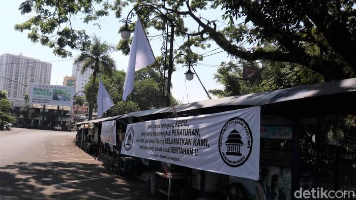 Pedagang kaki lima (PKL) di Bandung punya cara sendiri menyuarakan aspirasi mereka tolak PPKM Darurat diperpanjang. Salah satunya dengan kibarkan bendera putih.