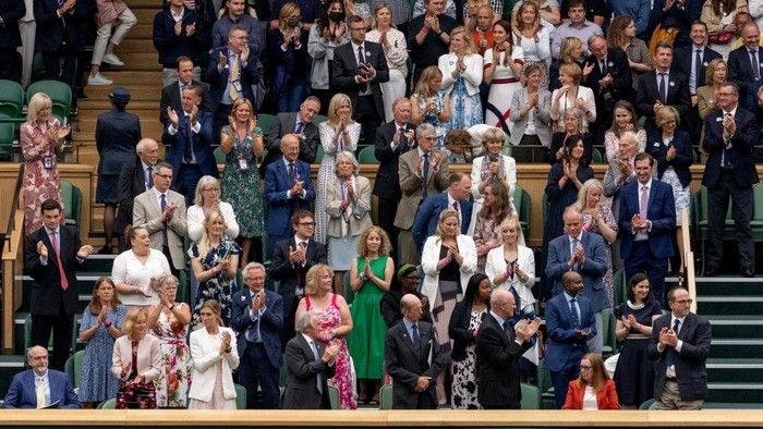 LONDON, ENGLAND - JUNE 28: The Royal Box stands and applauds University of Oxford Professor Sarah Gilbert (seated in red, bottom right) one of the people behind the Astra Zeneca COVID-19 vaccine ahead of the opening match on Centre Court during Day One of The Championships - Wimbledon 2021 at All England Lawn Tennis and Croquet Club on June 28, 2021 in London, England. (Photo by AELTC/Joe Toth-Pool/Getty Images)