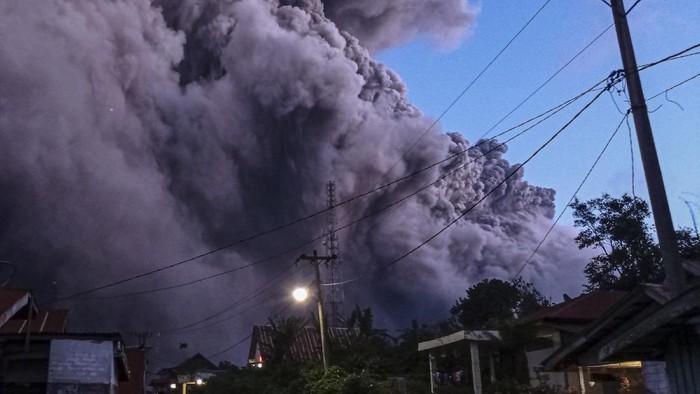 Warga mengamati Gunung Sinabung yang menyemburkan material vulkanik di Desa Kutarayat, Naman Teran, Karo, Sumatera Utara, Senin (19/7/2021). Gunung Sinabung erupsi dengan tinggi kolom 5.000 meter di atas puncak atau 3.460 m di atas permukaan laut. ANTARA FOTO/Sastrwawan Ginting/Lmo/aww.