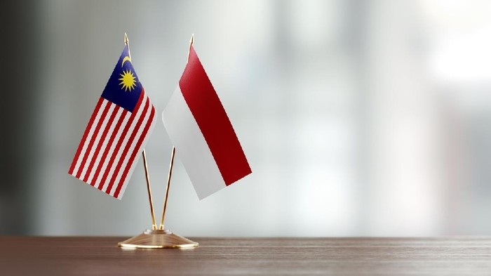 Malaysian and Indonesian flag pair on desk over defocused background. Horizontal composition with copy space and selective focus.