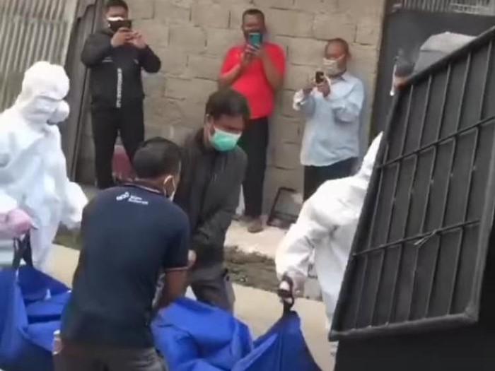 Petugas ber-APD gotong jenazah dari salah satu kontrakan di Bekasi (tangkapan layar)