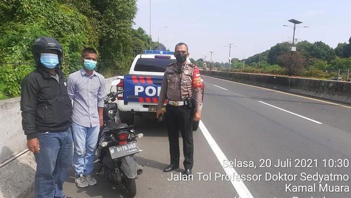 Petugas PJR Polda Metro Jaya mengamankan motor masuk Tol Sedyatmo, Jakarta Utara, Selasa (20/7/2021).