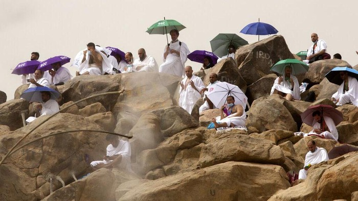 A Muslim pilgrim prays on top of the rocky hill known as the Mountain of Mercy, on the Plain of Arafat, during the annual hajj pilgrimage, near the holy city of Mecca, Saudi Arabia, Monday, July 19, 2021. The coronavirus has taken its toll on the hajj for a second year running. What once drew some 2.5 million Muslims from all walks of life from across the globe, the hajj pilgrimage is now almost unrecognizable in scale. (AP Photo/Amr Nabil)