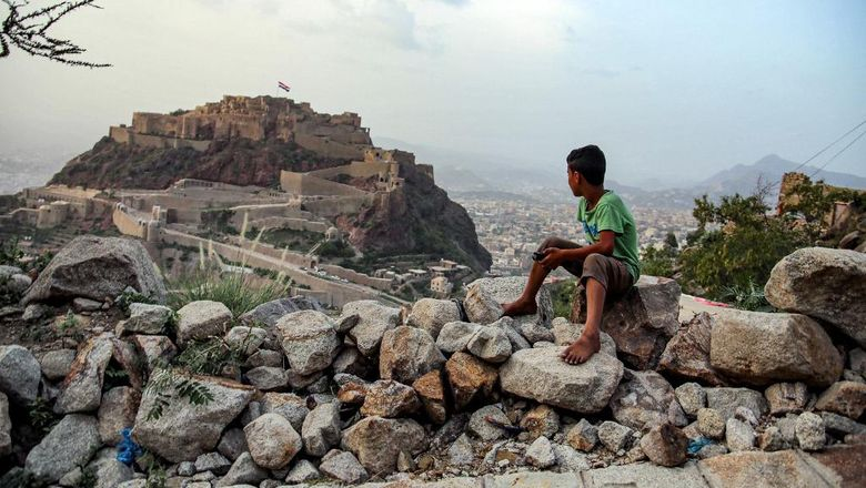 A boy looks at a giant Yemeni flag flying at the historic 12th cehntury citadel of al-Qahira in Yemens third city of Taez, on July 18, 2021, ahead of celebrations of the Muslim holiday of Eid al-Adha. - Known as the