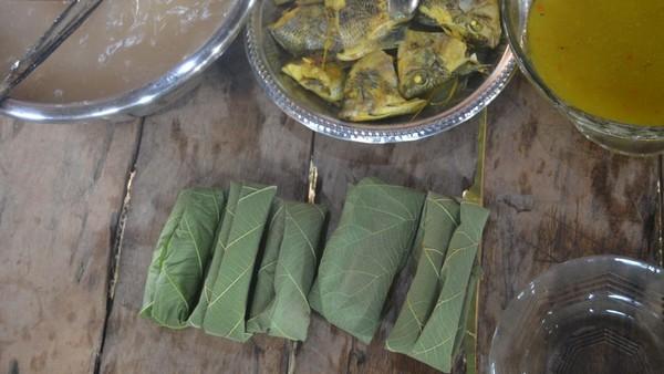 Papeda bungkus bisa dinikmati dengan lauk ikan kuah kuning dan sayur tumisan daun pepaya. Cara pembuatannya, papeda panas diambil secukupnya kemudian dibungkus daun. Diamkan beberapa saat, sampai papeda dingin, kemudian baru dapat dinikmati. (Hari Suroto/Istimewa)