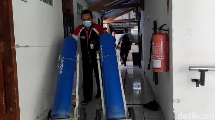 Petugas di RSU Holistik Purwakarta membawa dua tabung oksigen