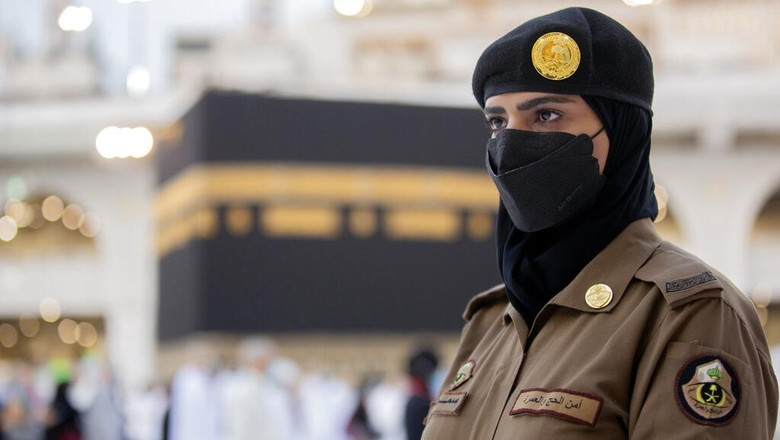 Saudi police woman, Bashair, left, adjusts the veil of her colleague Alaa, as they recently deployed to the service at the Grand Mosque, during the annual hajj pilgrimage, in the Saudi Arabias holy city of Mecca, Tuesday, July 20, 2021. (AP Photo/Amr Nabil)