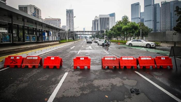 Kendaraan melintas di tempat penyekatan Pemberlakuan Pembatasan Kegiatan Masyarakat (PPKM) Darurat di Jalan Jenderal Sudirman, Jakarta, Senin (19/7/2021). Pemerintah masih mempertimbangkan rencana perpanjangan masa PPKM darurat Jawa-Bali yang akan berakhir pada Selasa (20/7/2021). ANTARA FOTO/Rivan Awal Lingga/aww.