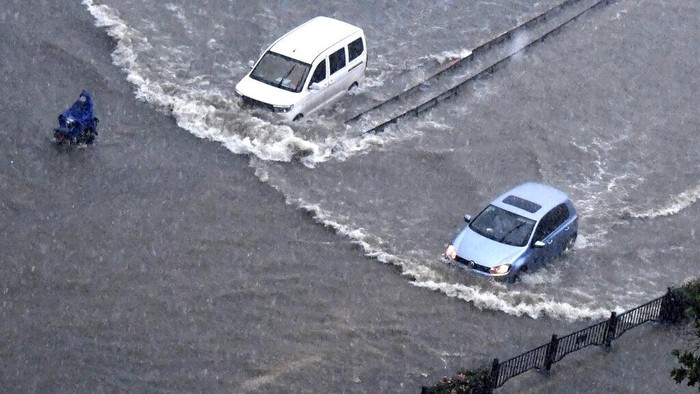 In this photo released by Xinhua News Agency, vehicles pass through floodwaters in Zhengzhou in central Chinas Henan Province on Tuesday, July 20, 2021. At least a dozen people died in severe flooding Tuesday in a Chinese provincial capital that trapped people in subways and schools, washed away vehicles and stranded people in their workplaces overnight. (Zhu Xiang/Xinhua via AP)