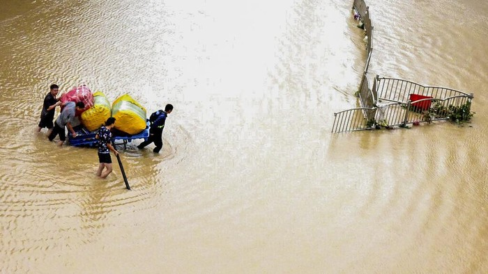 In this photo released by Xinhua News Agency, residents move their belongings across a flooded street in Zhengzhou in central Chinas Henan province on Wednesday, July 21, 2021. Chinas military has blasted a dam to release floodwaters threatening one of its most heavily populated provinces, as the death toll in widespread flooding rose to more than two dozens. (Zhu Xiang/Xinhua via AP)