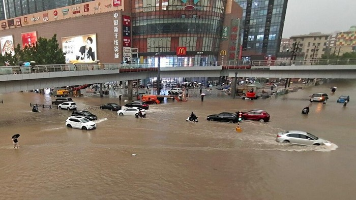 People move through flood water after a heavy downpour in Zhengzhou city, central Chinas Henan province on Tuesday, July 20, 2021. Heavy flooding has hit central China following unusually heavy rains, with the subway system in the city of Zhengzhou inundated with rushing water and thousands of residents having to be relocated. (Chinatopix Via AP)