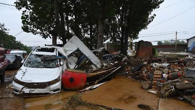 Damaged cars and debris are seen on a muddy road after severe flooding and landslide in recent days have hit the county-level Gongyi city, near Zhengzhou, in central Chinas Henan province on July 22, 2021. (Photo by JADE GAO / AFP)