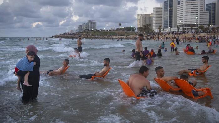 Libur Idul Adha dimanfaatkan sebagian warga Palestina dengan berwisata ke pantai di Tel Aviv, Israel. Begini momennya.