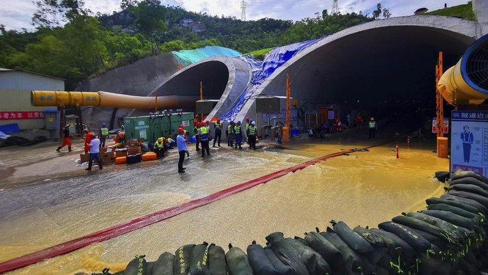 Rescuers build embankments to pump out water from a flooded tunnel in Zhuhai city in south Chinas Guangdong province Friday, July 16, 2021. Divers have been dispatched in the search for 14 workers missing since water flooded a tunnel under construction in southern China three days ago, authorities said Sunday, July 18, 2021. (Chinatopix via AP)