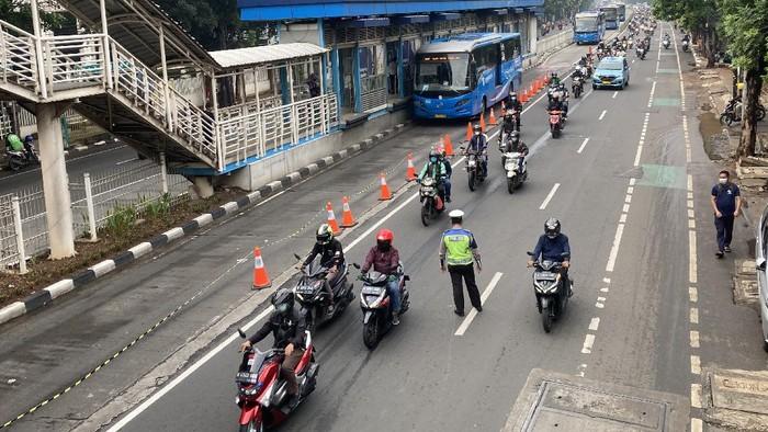 Polisi melonggarkan penyekatan di depan Halte TransJakarta Mampang Prapatan, Jakarta Selatan, Jumat (23/7/2021).