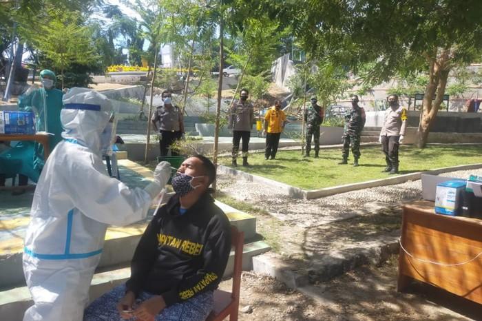 Polisi dan TNI mengawasi tes cepat antigen bagi seorang pria yang sempat ikut mengambil paksa jenazah pasien COVID-19 (ANTARA/Ho-Humas Polres Kupang Kota)
