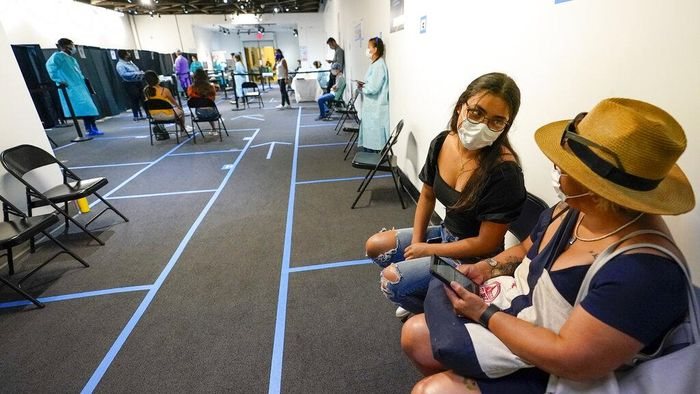 Mia Fontes, 15 shows the stickers she received after being inoculated with the second dose of the Pfizer COVID-19 vaccine, Thursday, July 22, 2021, at the American Museum of Natural History in New York. The museum moved their vaccination site from the Hall of Ocean Life where the famous 94-foot-long model of a blue whale is hanging from the ceiling to a smaller adjacent gallery. New York City is closing the big vaccination sites to focus on areas with low vaccination rates. (AP Photo/Mary Altaffer)