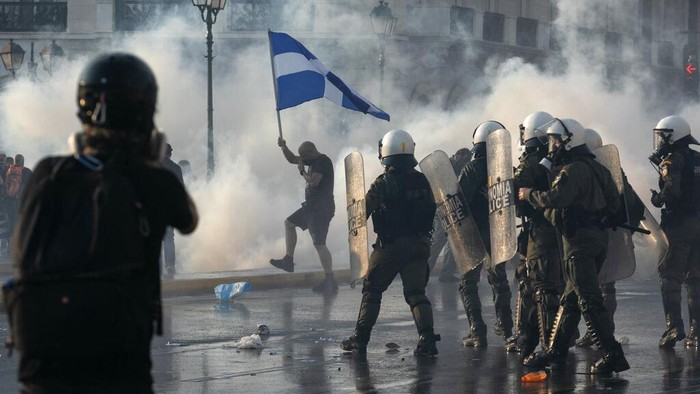 Greek police use tear gas and water cannons to disperse anti-vaccine protesters during a rally at Syntagma square, central Athens, on Wednesday, July 21, 2021. Thousands of people protested against Greek governments measures to curb rising COVID-19 infections and drive up vaccinations in the country where almost 50% of Greeks and country residents have received at least one dose of the vaccine. (AP Photo/Yorgos Karahalis)