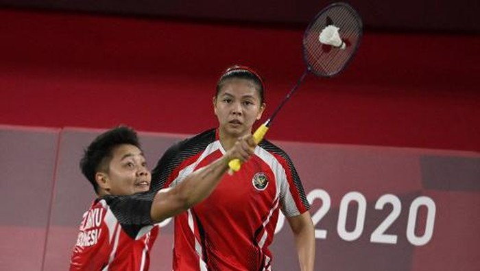 Indonesias Greysia Polii (C) watches as Indonesias Apriyani Rahayu hits a shot in their womens doubles badminton group stage match against Malaysias Lee Meng Yean and Malaysias Chow Mei Kuan during the Tokyo 2020 Olympic Games at the Musashino Forest Sports Plaza in Tokyo on July 24, 2021. (Photo by Alexander NEMENOV / AFP)