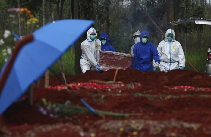 Workers in protective suits carry a coffin containing the body of a COVID-19 victim to a grave for burial at Cipenjo cemetery in Bogor, West Java, Indonesia on July 14, 2021. With the numbers of death increasing from the latest virus surge in Indonesia which has crippled the healthcare system in Java and Bali, relatives and residents decided to volunteer to dig graves using their own hoes and shovels to help exhausting gravediggers. (AP Photo/Achmad Ibrahim)