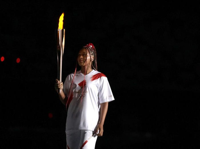 TOKYO, JAPAN - JULY 23: Naomi Osaka of Team Japan carries the Olympic torch towards the Olympic cauldron during the Opening Ceremony of the Tokyo 2020 Olympic Games at Olympic Stadium on July 23, 2021 in Tokyo, Japan. (Photo by Ezra Shaw/Getty Images)