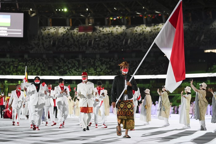 TOKYO, JAPAN - JULY 23: Flag bearer Nurul Akmal of Team Indonesia leads his team out during the Opening Ceremony of the Tokyo 2020 Olympic Games at Olympic Stadium on July 23, 2021 in Tokyo, Japan. (Photo by Matthias Hangst/Getty Images)
