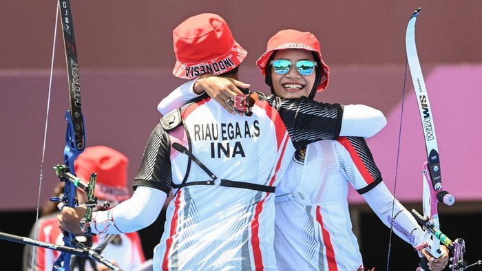 Indonesias Diananda Choirunisa (R) and Riau Salsabila celebrate after beating the USA in the mixed team eliminations during the Tokyo 2020 Olympic Games at Yumenoshima Park Archery Field in Tokyo on July 24, 2021. (Photo by ADEK BERRY / AFP)