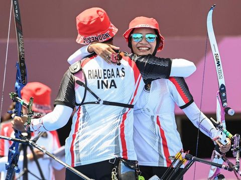 Indonesia's Diananda Choirunisa (R) and Riau Salsabila celebrate after beating the USA in the mixed team eliminations during the Tokyo 2020 Olympic Games at Yumenoshima Park Archery Field in Tokyo on July 24, 2021. (Photo by ADEK BERRY / AFP)