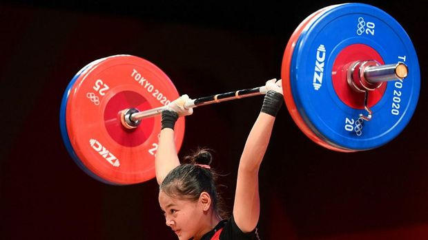 Indonesia's Windy Cantika Aisah competes in the women's 49kg weightlifting competition during the Tokyo 2020 Olympic Games at the Tokyo International Forum in Tokyo on July 24, 2021. (Photo by Vincenzo PINTO / AFP)