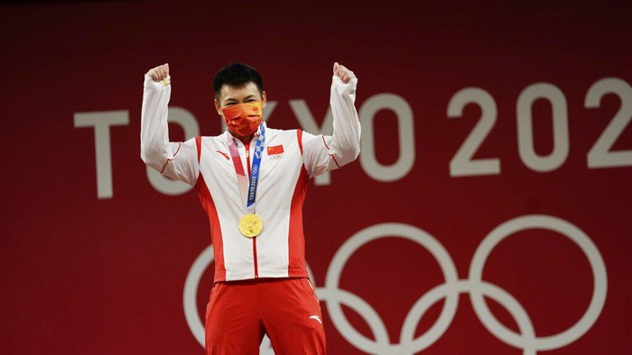 Chen Lijun of China celebrates on the podium after winning the gold medal and setting an Olympic record in the mens 67kg weightlifting event, at the 2020 Summer Olympics, Sunday, July 25, 2021, in Tokyo, Japan. (AP Photo/Luca Bruno)