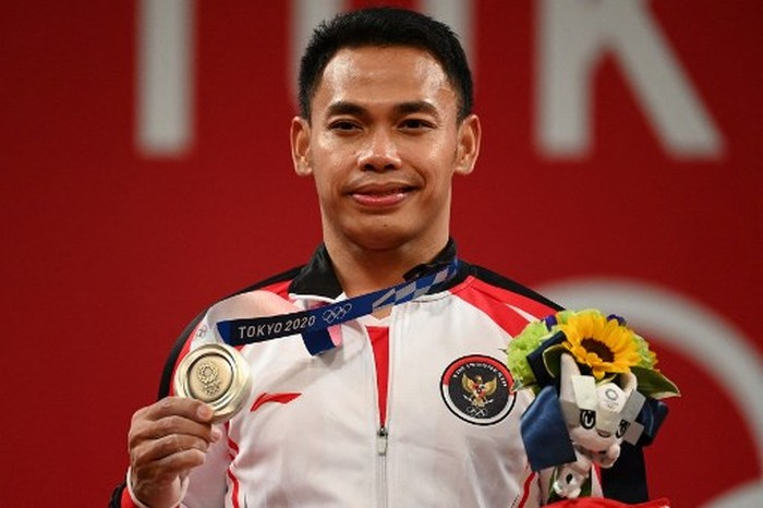 Silver medallist Indonesias Eko Yuli Irawan stands on the podium for the victory ceremony of the mens 61kg weightlifting competition during the Tokyo 2020 Olympic Games at the Tokyo International Forum in Tokyo on July 25, 2021. (Photo by Vincenzo PINTO / AFP)
