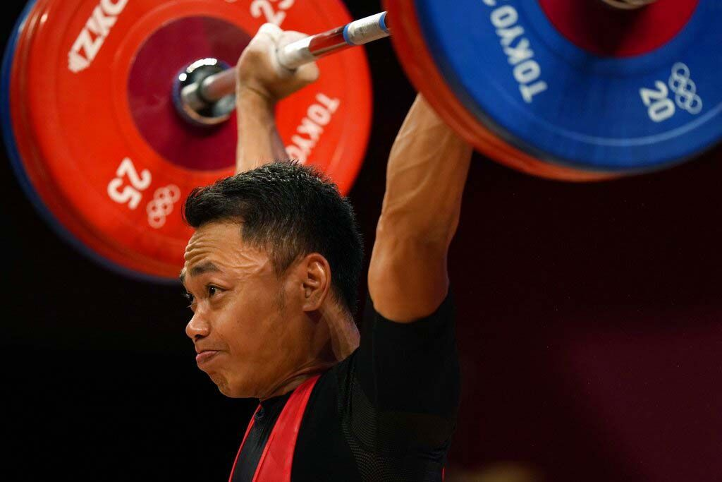 Li Fabin of China , gold medal, right, celebrates on the podium with silver medal Eco Yuli Irawan of Indonesia in the men's 61kg weightlifting event, at the 2020 Summer Olympics, Sunday, July 25, 2021, in Tokyo, Japan. (AP Photo/Luca Bruno)