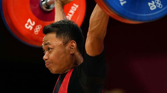 Li Fabin of China , gold medal, right, celebrates on the podium with silver medal Eco Yuli Irawan of Indonesia in the mens 61kg weightlifting event, at the 2020 Summer Olympics, Sunday, July 25, 2021, in Tokyo, Japan. (AP Photo/Luca Bruno)