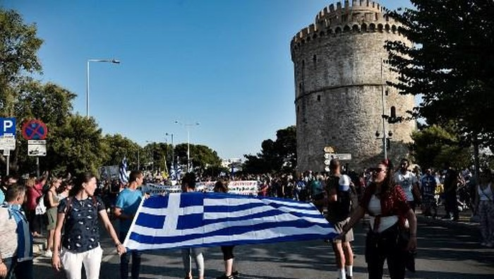 Anti-vaccine protesters hold a flag of Greece as they take part in a rally in Thessaloniki on July 21, 2021. - About 5,000 people demonstrated in Greece on July 21, 2021, including 3,000 in central Athens, against the compulsory vaccination of caregivers and nursing home staff, according to police. (Photo by Sakis MITROLIDIS / AFP)