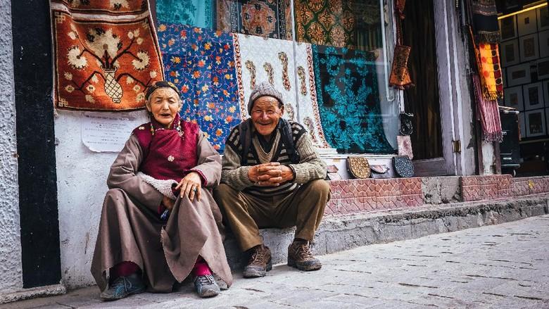 Leh , Ladakh region , India - August 20, 2016: Old Ladakhi people couple carpet sellers sitting on the street in Leh, India