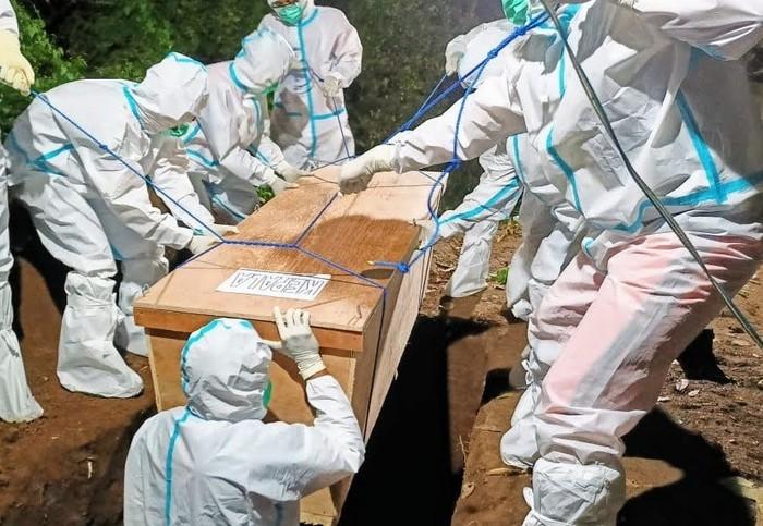relawan tim pemulasaraan jenazah saat memakamkan pasien COVID-19