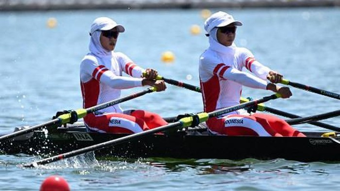 (L-R) Indonesias Mutiara Putri and Indonesias Melani Putri compete in the lightweight womens double sculls repechage during the Tokyo 2020 Olympic Games at the Sea Forest Waterway in Tokyo on July 25, 2021. (Photo by Charly TRIBALLEAU / AFP)