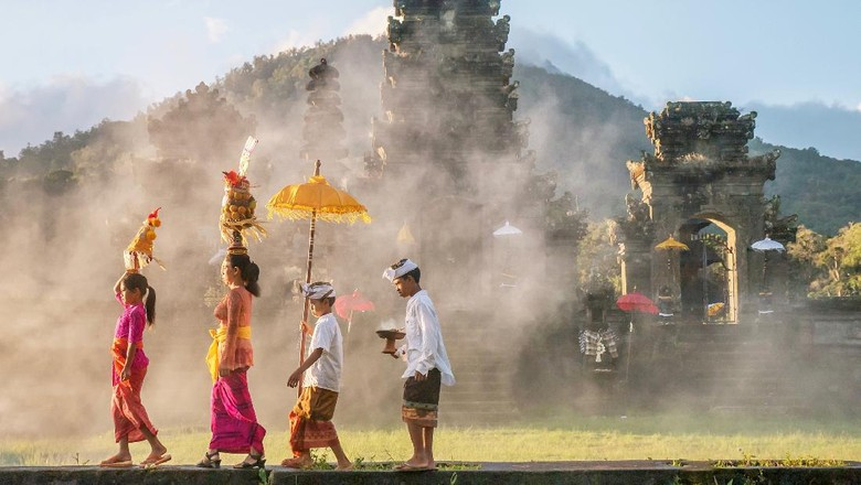 A mother and a teenaged girl are dressed in brightly colored sarongs, blouses, and sashes and are balancing tall fruit baskets on their heads. Two sons are dressed in sarongs and white shirts. The family is walking in front of an old stone temple building which has a smoky atmosphere.
