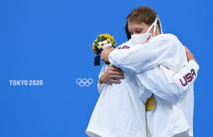 Silver medallist USAs Jay Litherland (L) and gold medallist USAs Chase Kalisz hug each other on the podium after the final of the mens 400m individual medley swimming event during the Tokyo 2020 Olympic Games at the Tokyo Aquatics Centre in Tokyo on July 25, 2021. (Photo by Jonathan NACKSTRAND / AFP) / The erroneous mention[s] appearing in the metadata of this photo by Jonathan NACKSTRAND has been modified in AFP systems in the following manner: [Silver medallist USAs Jay Litherland] instead of [Bronze medallist USAs Jay Litherland]. Please immediately remove the erroneous mention[s] from all your online services and delete it (them) from your servers. If you have been authorized by AFP to distribute it (them) to third parties, please ensure that the same actions are carried out by them. Failure to promptly comply with these instructions will entail liability on your part for any continued or post notification usage. Therefore we thank you very much for all your attention and prompt action. We are sorry for the inconvenience this notification may cause and remain at your disposal for any further information you may require.