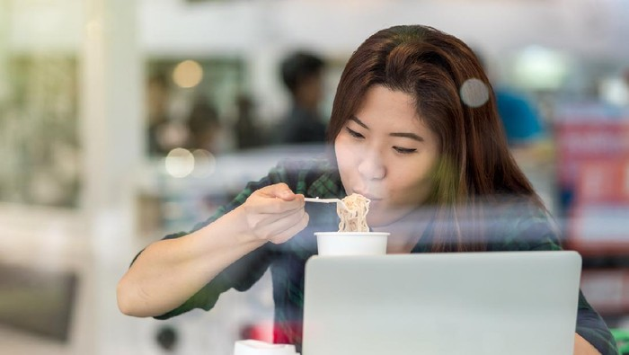 Portrait of asian businesswoman in casual suit eating noodles with happiness action in rush hour at the desk beside the glass in modern office, Business work hard concept