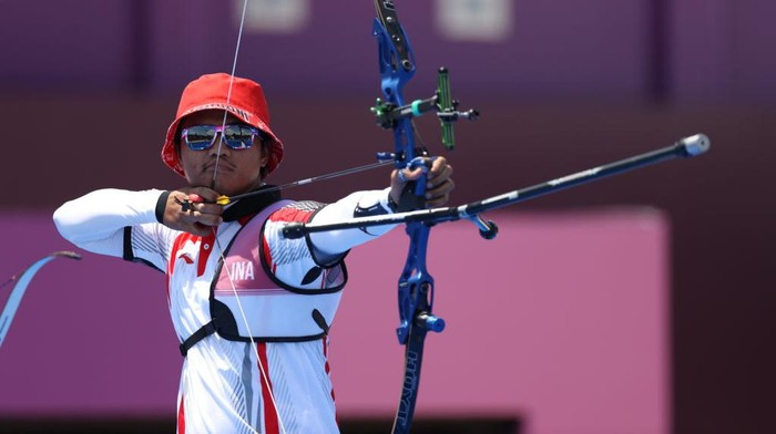 TOKYO, JAPAN - JULY 24: Riau Ega Salsabilla of Team Indonesia competes in the Mixed Team 1/8 Eliminations on day one of the Tokyo 2020 Olympic Games at Yumenoshima Park Archery Field on July 24, 2021 in Tokyo, Japan. (Photo by Justin Setterfield/Getty Images)