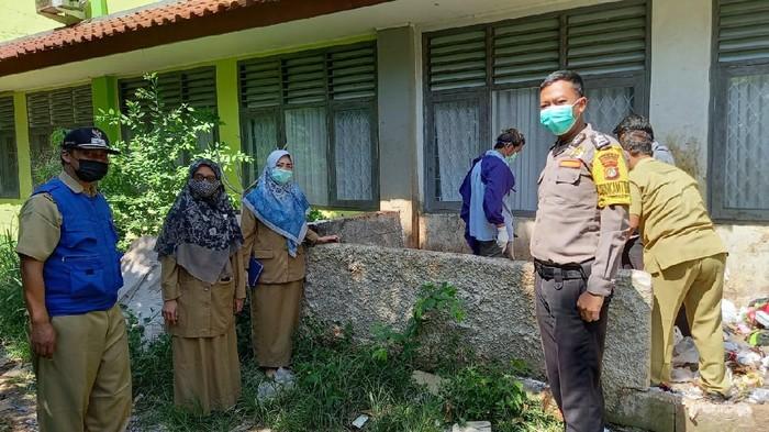 Petugas membersihkan sampah jarum suntik bekas vaksin yang dibuang ke tempat sampah di SMK di Depok (Dok.Istimewa). Foto dikirim Plt Camat Tapos, Anwar.